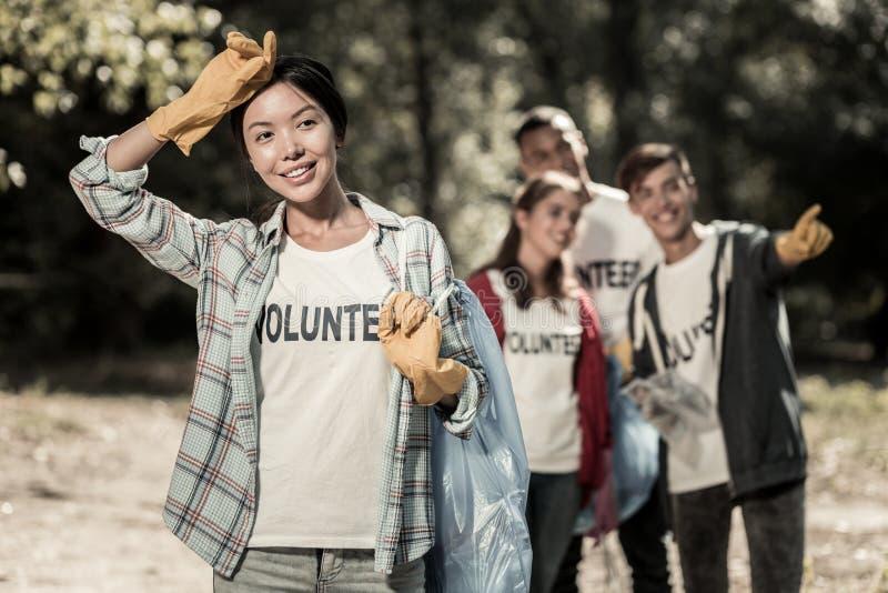 Donker-haired slanke vrouw die vrolijk na het deelnemen aan vrijwilligersactiviteit voelen royalty-vrije stock afbeeldingen