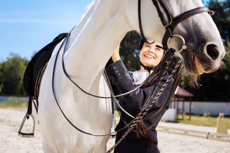 Donker-haired vrouwelijke ruiter die met lange vlecht haar paard behandelen stock afbeeldingen