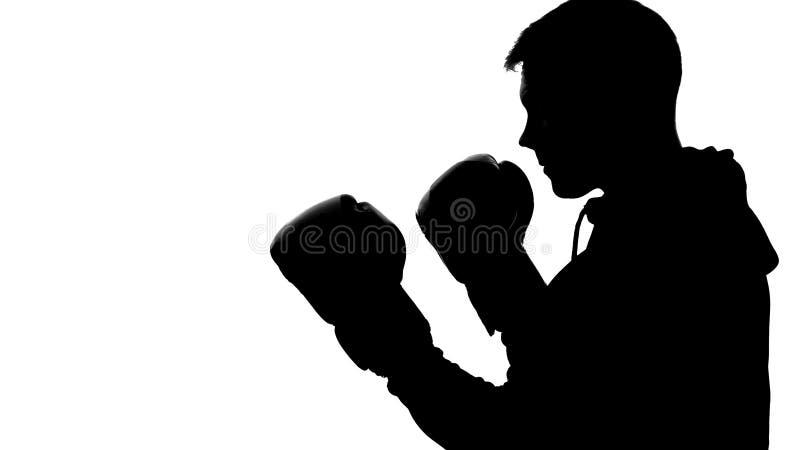 Donker mannelijk silhouet in kap aanvallende tegenstander, schaduw-in dozen doende zelf-defensie stock afbeeldingen