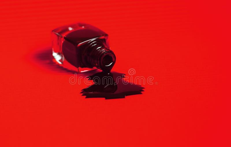 Donker nagellak dat van de fles wordt gemorst trillende rode achtergrond stock foto