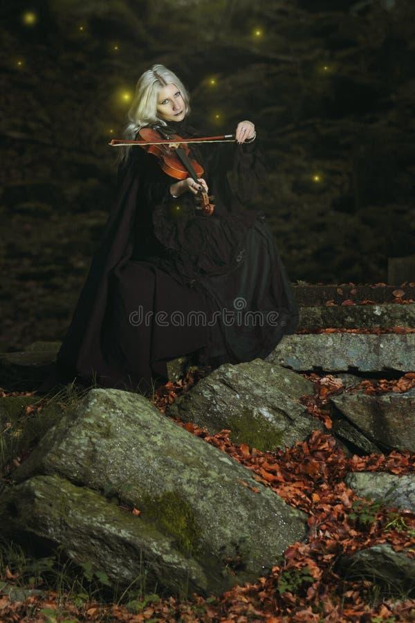 Donker portret van een vampier met viool stock foto