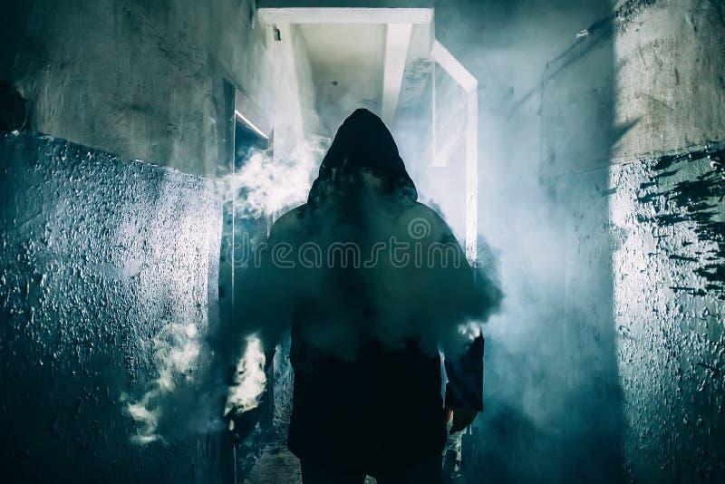 Donker silhouet van de vreemde gevaarsmens in kap in achterlicht met rook of mist in enge grungegang of tunnel stock afbeeldingen
