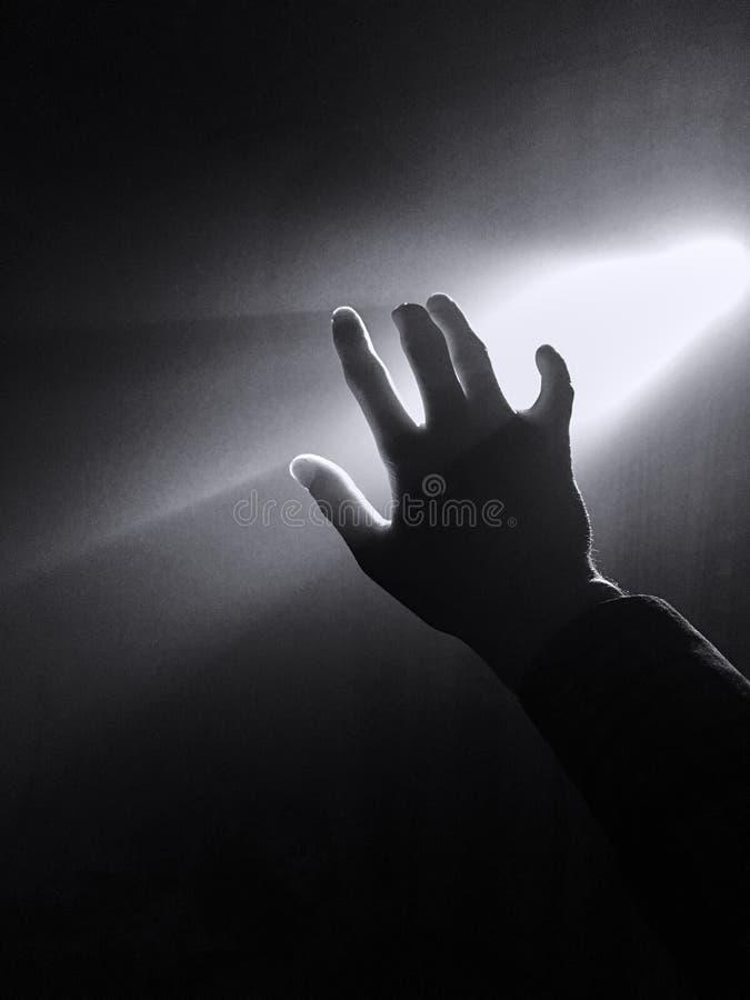 donker silhouet van menselijke mannelijke hand met vingers in schijnwerper of backlight licht met gebaar op zwarte achtergrond me royalty-vrije stock fotografie