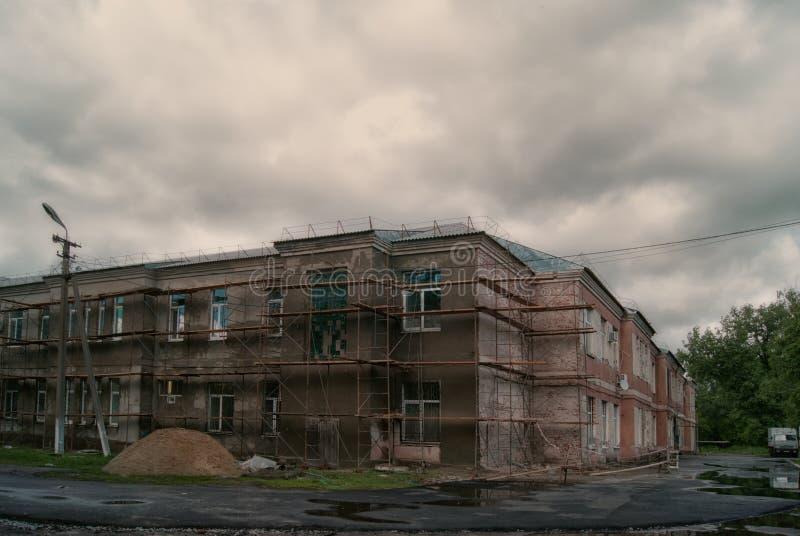 Donker somber dubbel-verdiepingshuis onder een bewolkte hemel stock foto