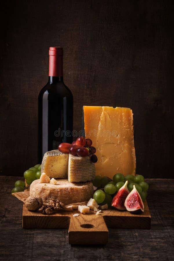 Donker stilleven met kaasraad, vruchten en wijn royalty-vrije stock foto
