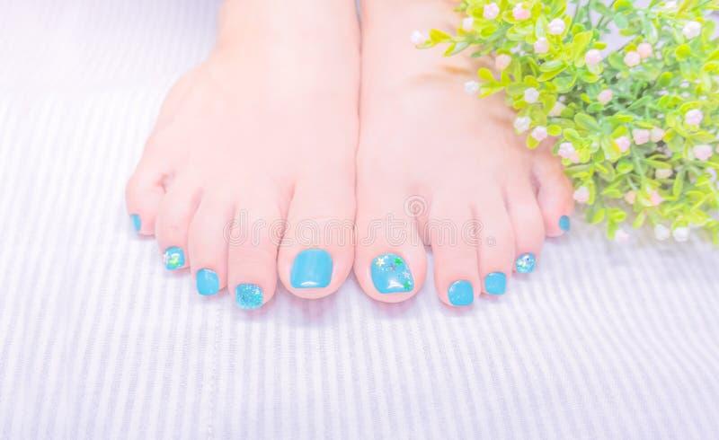 Donkerblauw groen gelpoetsmiddel op teennagel met leuk ontwerp stock foto