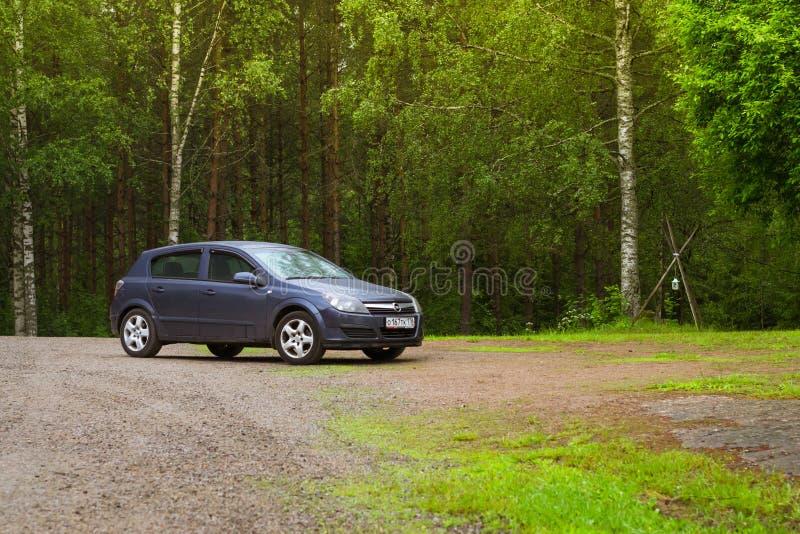 Donkerblauw Opel Astra H op een groene weide Palvaanjarvenkampeerterrein royalty-vrije stock afbeeldingen