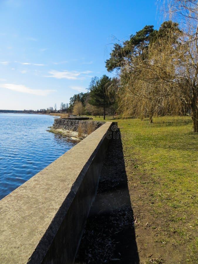Donkerblauw water op de Lielupe-Rivier in Letland in de vroege lente dijk stock afbeeldingen