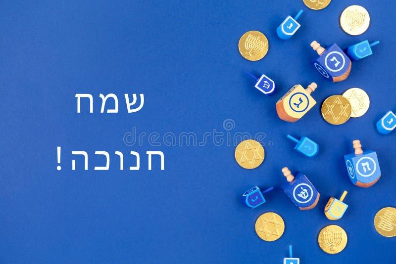Donkerblauwe achtergrond met meerkleurige droidels en chocolade-munten en Happy Hanukkah-tekst in het Hebreeuws stock foto's