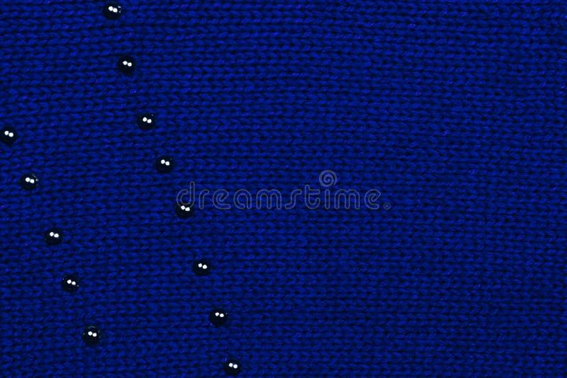 Donkerblauwe gebreide stof met zichtbaar gebreid patroon en het zwarte ornament van metaalpunten Hoogste mening De ruimte van het royalty-vrije stock afbeeldingen