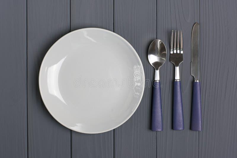 Donkerblauwe lepel, vork, mes, grijze plaat op een grijze houten achtergrond royalty-vrije stock foto
