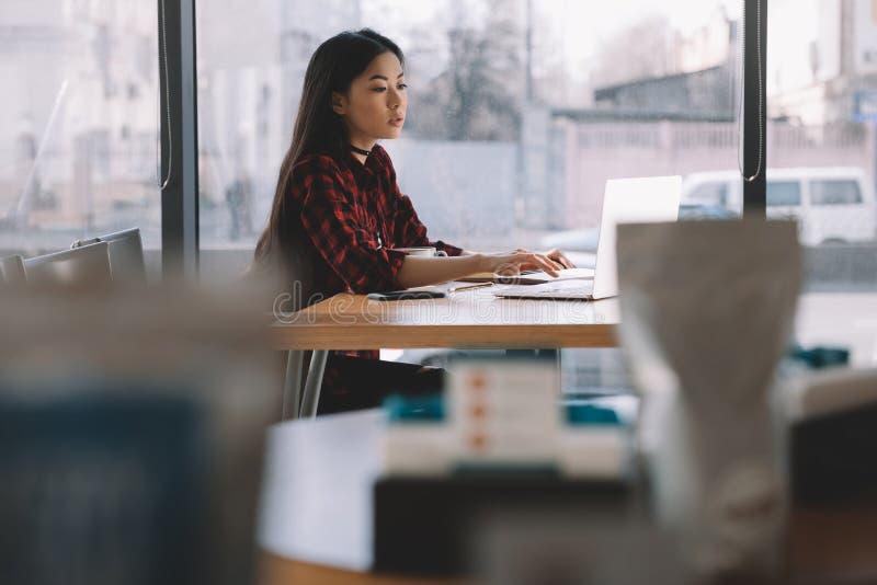 Donkerbruin Aziatisch meisje die laptop computer in koffie met behulp van royalty-vrije stock foto's