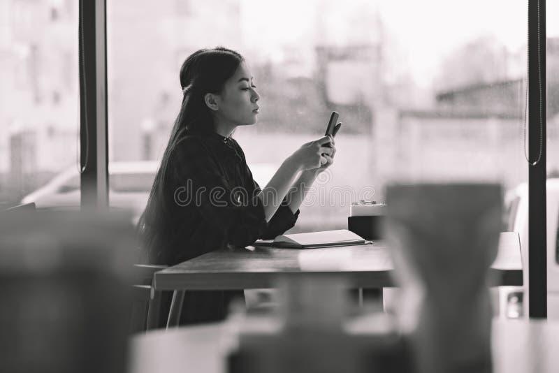 Donkerbruin Aziatisch meisje die smartphone in zwart-witte koffie gebruiken, royalty-vrije stock afbeeldingen