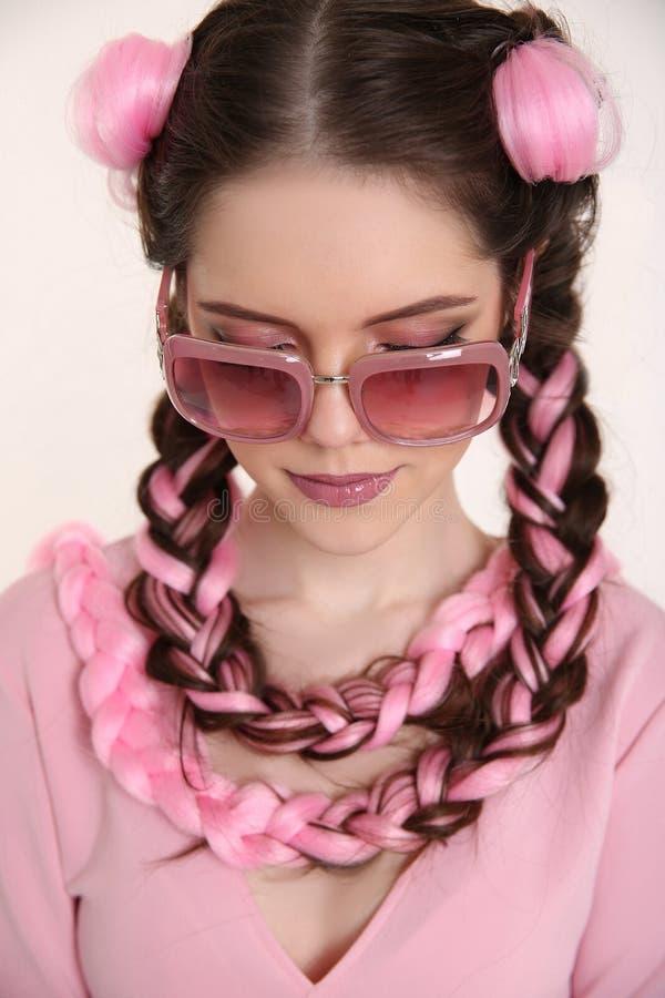 Donkerbruin die tienermeisje met twee Franse vlechten van roze kane wordt gevlecht stock fotografie