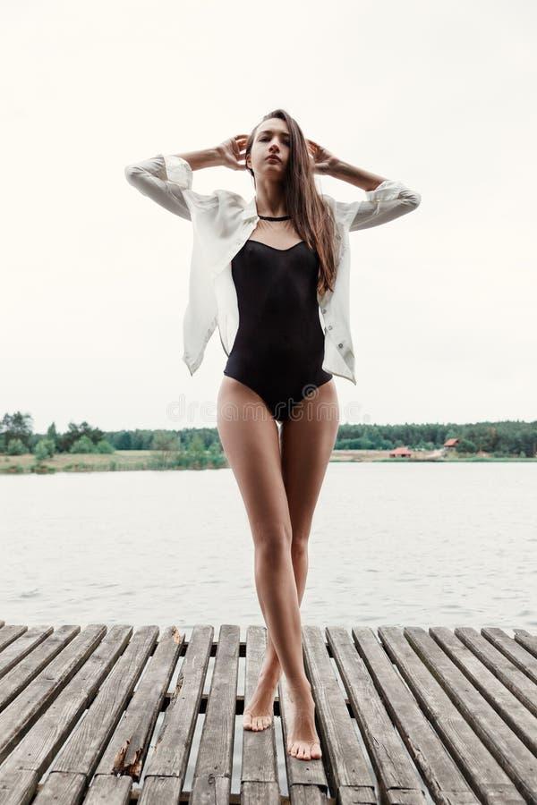 Donkerbruin Europees meisje in zwarte bikini op de brug stock afbeeldingen