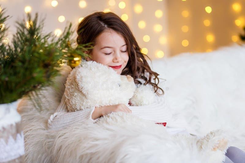 Donkerbruin gilr voor bont-boom en open haard met kaarsen en giften Meisje het dromen Nieuwjaar` s Vooravond Kerstmis stock fotografie