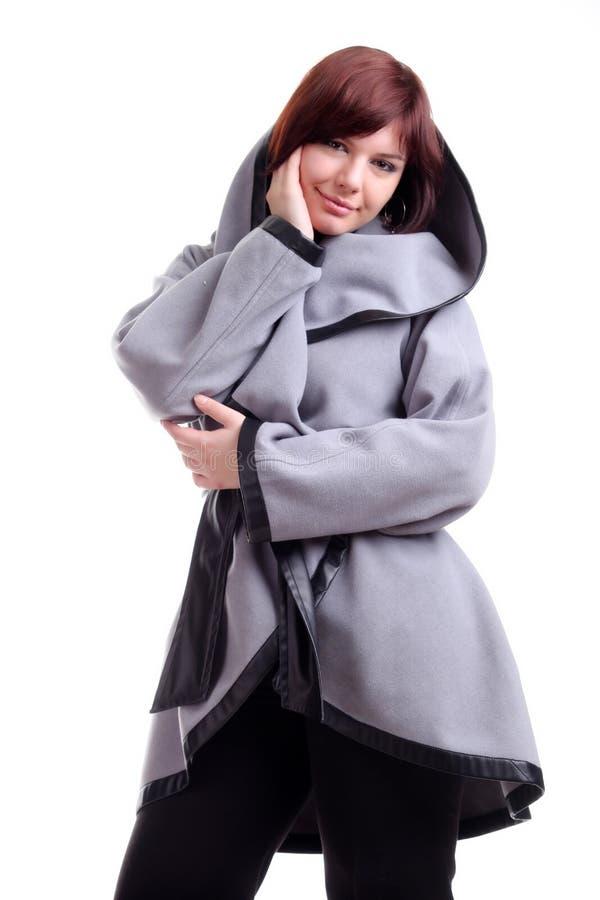 donkerbruin kortharig meisje in modieuze grijze laag stock foto