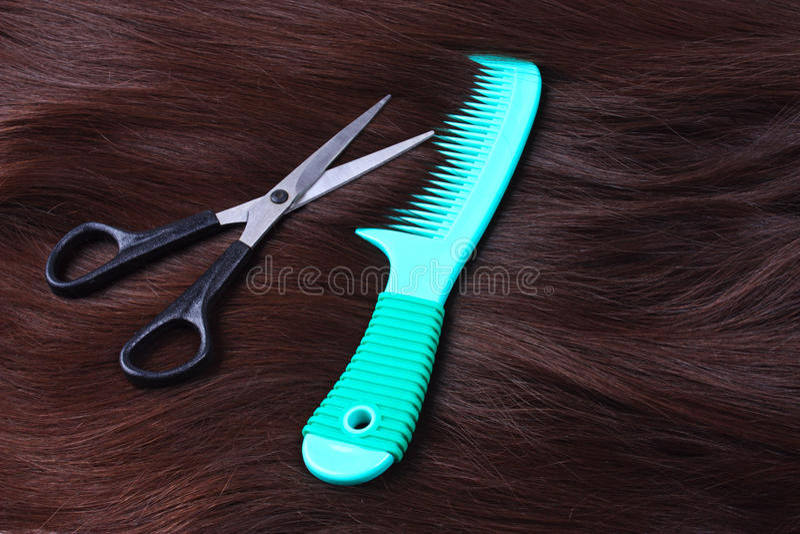 Donkerbruin lang haar met groene kam en schaar stock fotografie