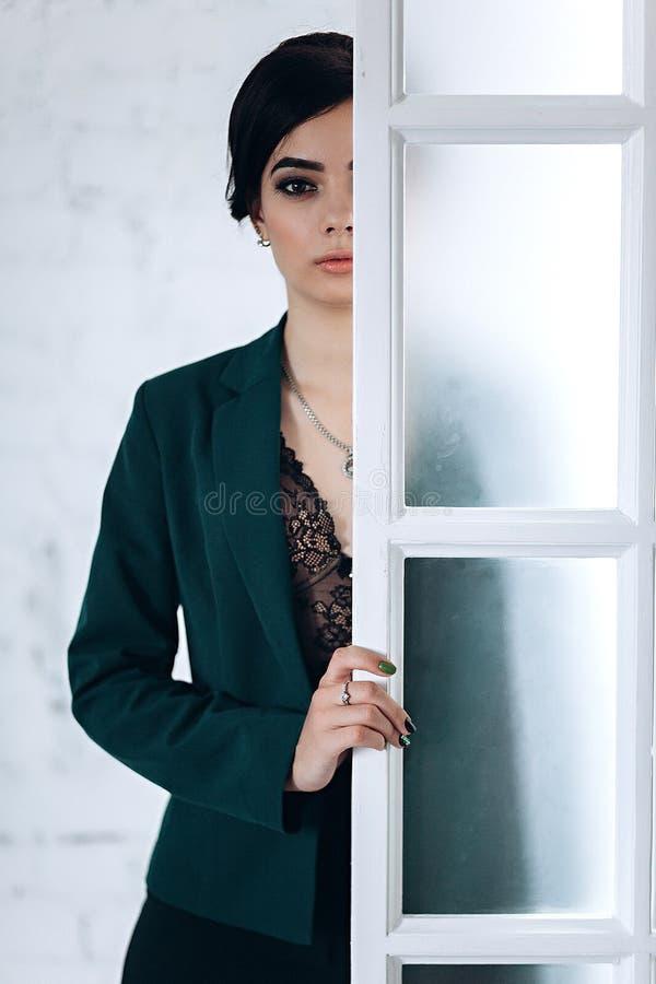 Donkerbruin meisje dichtbij de witte bakstenen muur royalty-vrije stock afbeeldingen