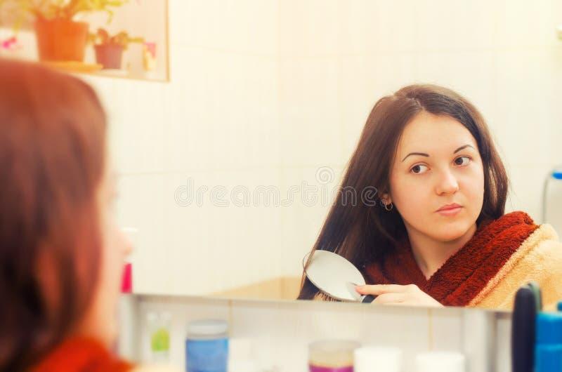 Donkerbruin meisje die haar haar kammen die in het spiegelconcept kijken schoonheid royalty-vrije stock foto's