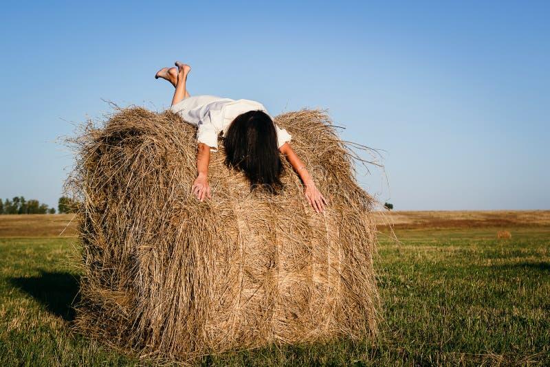 Donkerbruin meisje die op een hooiberg liggen stock afbeelding