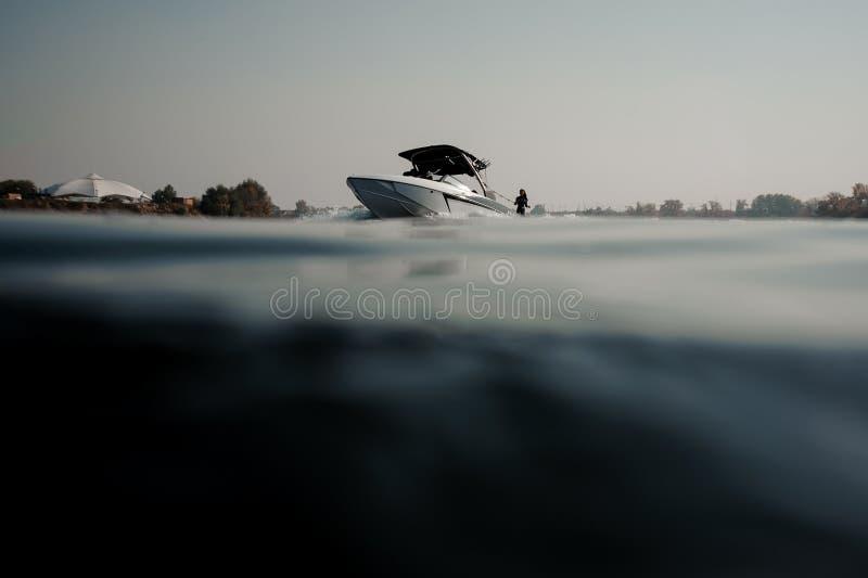 Donkerbruin meisje die op wakeboard berijden die een kabel op de motorboot houden royalty-vrije stock fotografie