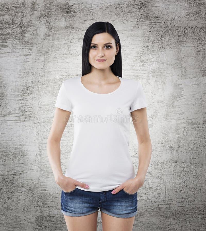 Donkerbruin meisje in een witte t-shirt en denimborrels stock afbeeldingen