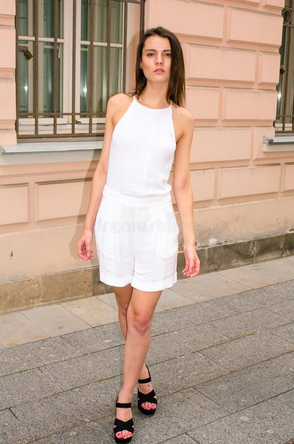 Donkerbruin meisje in het witte kleding stellen op de straat van de oude stad royalty-vrije stock foto