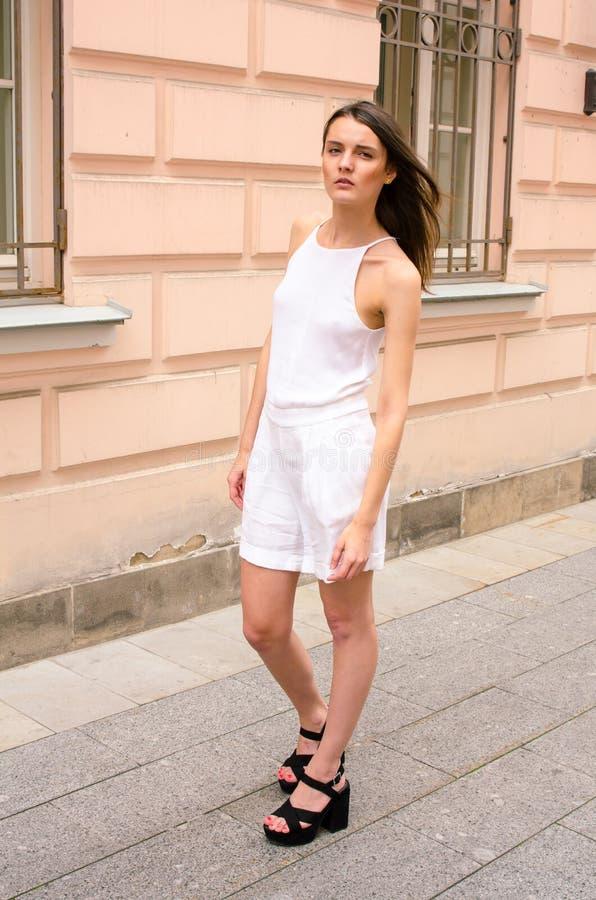Donkerbruin meisje in het witte kleding stellen op de straat van de oude stad stock foto