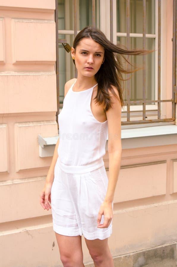 Donkerbruin meisje in het witte kleding stellen op de straat van de oude stad royalty-vrije stock afbeelding