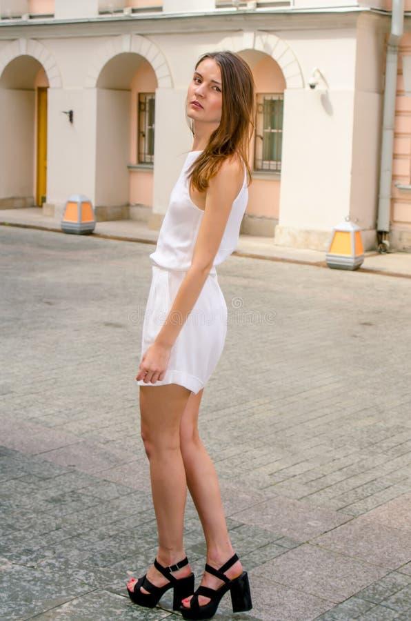 Donkerbruin meisje in het witte kleding stellen op de straat van de oude stad stock afbeelding