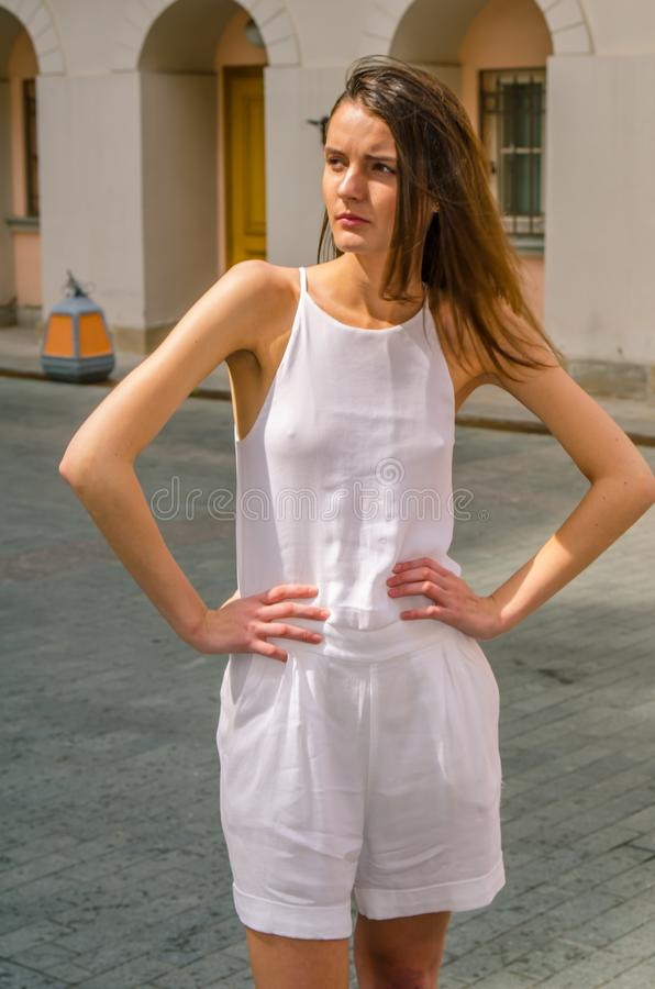 Donkerbruin meisje in het witte kleding stellen op de straat van de oude stad royalty-vrije stock fotografie