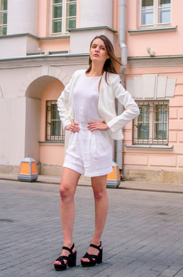 Donkerbruin meisje in het witte kleding stellen op de straat van de oude stad stock afbeeldingen