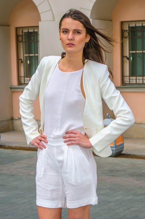 Donkerbruin meisje in het witte kleding stellen op de straat van de oude stad royalty-vrije stock afbeeldingen