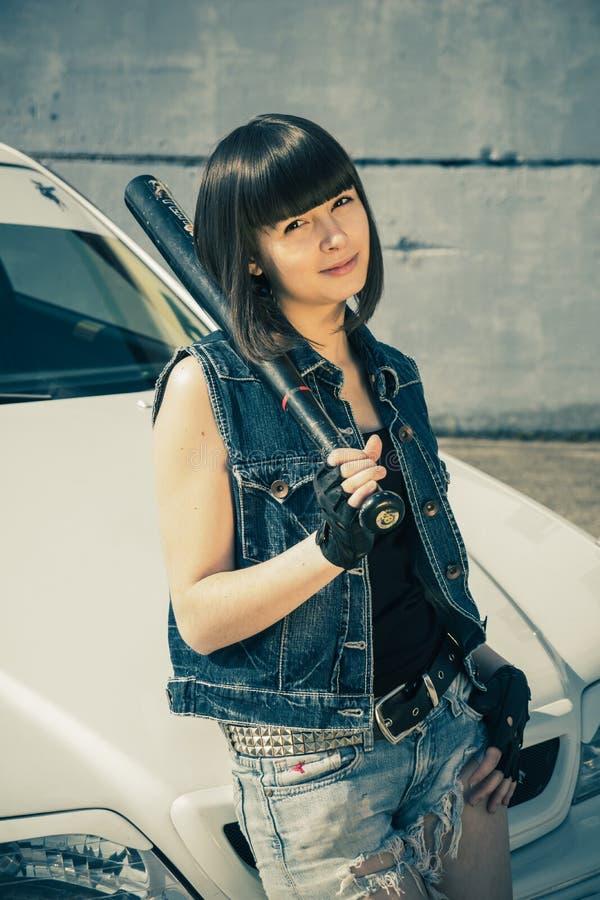 Donkerbruin meisje in korte denimborrels met een knuppel royalty-vrije stock afbeeldingen
