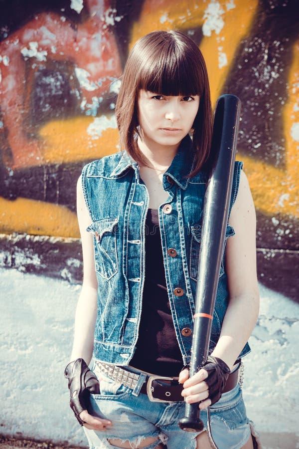 Donkerbruin meisje in korte denimborrels met een knuppel stock afbeeldingen