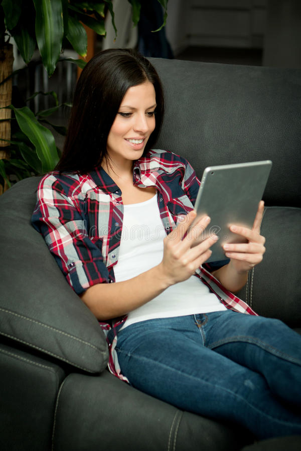 Donkerbruin meisje met een tablet thuis stock fotografie