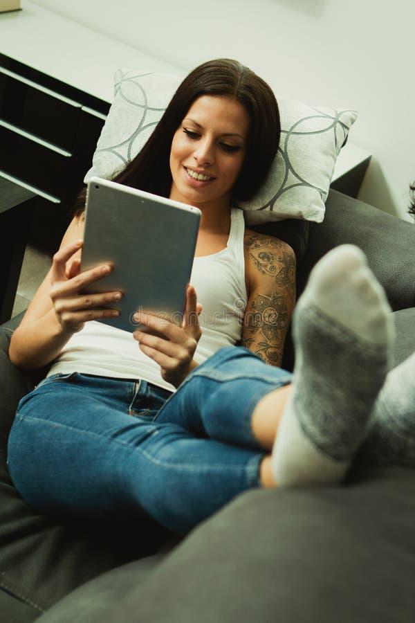 Donkerbruin meisje met een tablet thuis stock foto