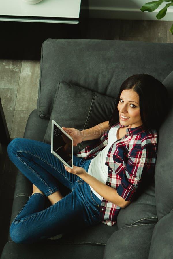 Donkerbruin meisje met een tablet thuis royalty-vrije stock afbeelding