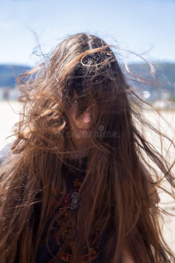 Donkerbruin meisje met lang haar die in de wind vliegen royalty-vrije stock afbeelding