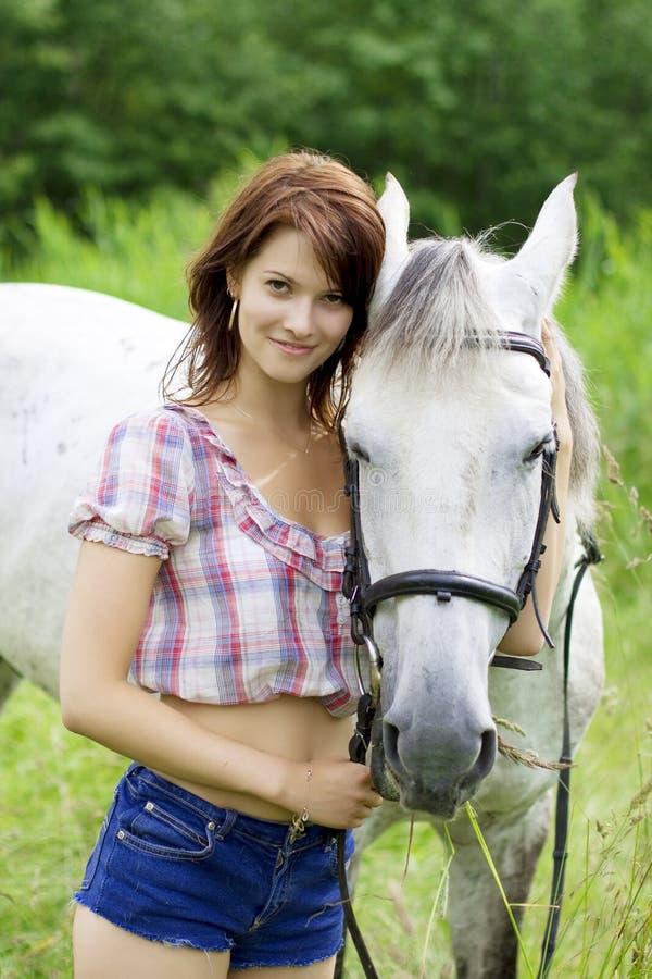 Donkerbruin meisje met paard stock fotografie