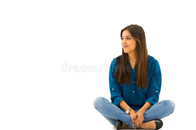 Donkerbruin model die vrijetijdskleding zitten dragen comfortabel op witte achtergrond die aan camera glimlachen stock afbeelding