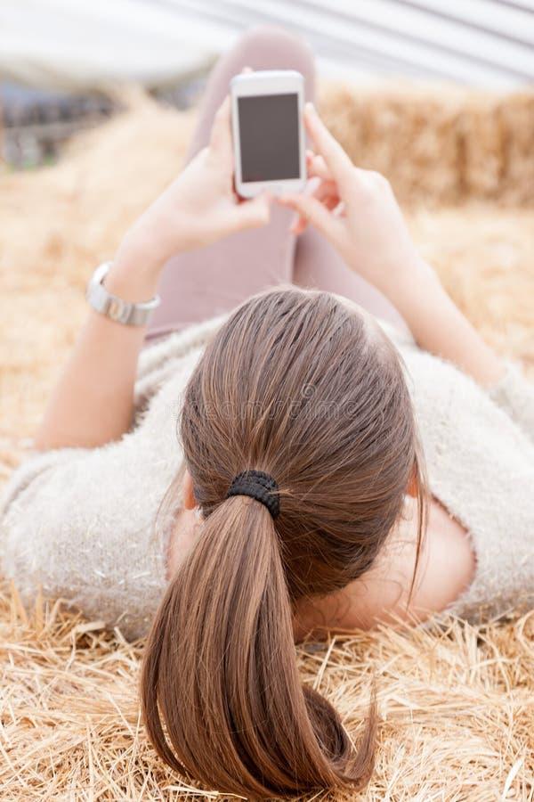 Donkerbruin tienermeisje die een tekst die op liggen hooibergen verzenden royalty-vrije stock foto
