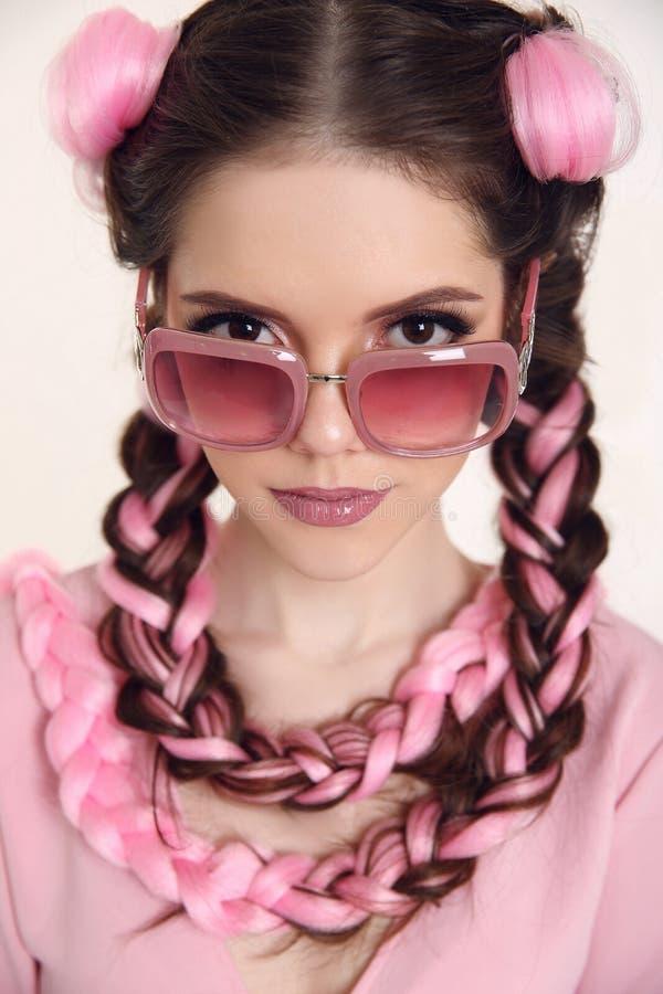 Donkerbruin tienermeisje met twee Franse vlechten van roze kanekalon, F stock foto's