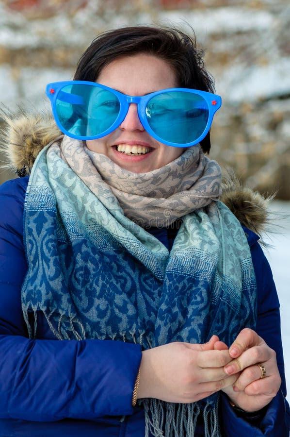 Donkerbruin volwassen meisje in grote clownglazen met sjaal, het glimlachen, die zich alleen openlucht in de koude winter bevinde stock fotografie
