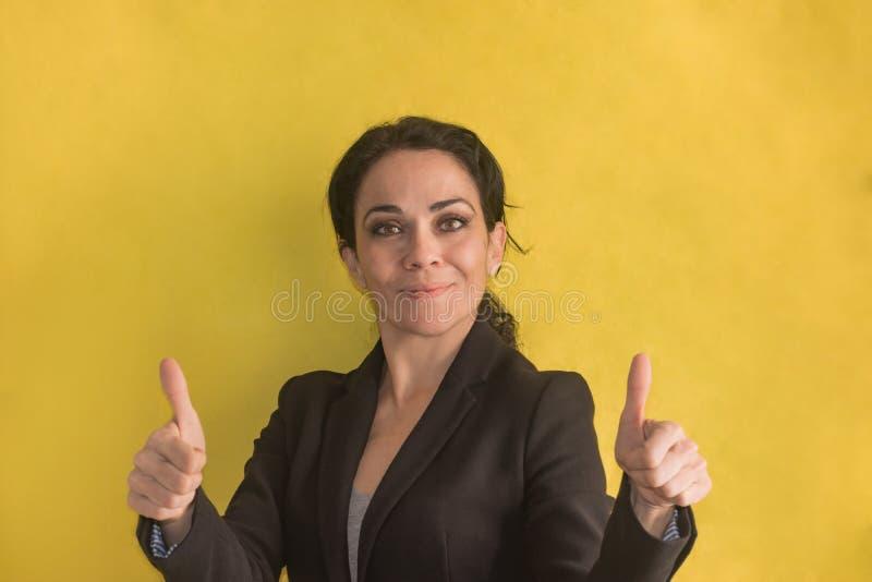 Donkerbruine bedrijfsvrouw over achtergrond die gelukkige duimen omhoog maken royalty-vrije stock foto's