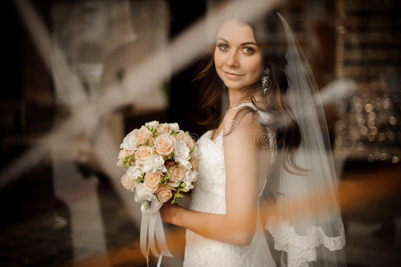 Donkerbruine bruid die en huwelijksboeket van rozen glimlachen houden royalty-vrije stock afbeelding