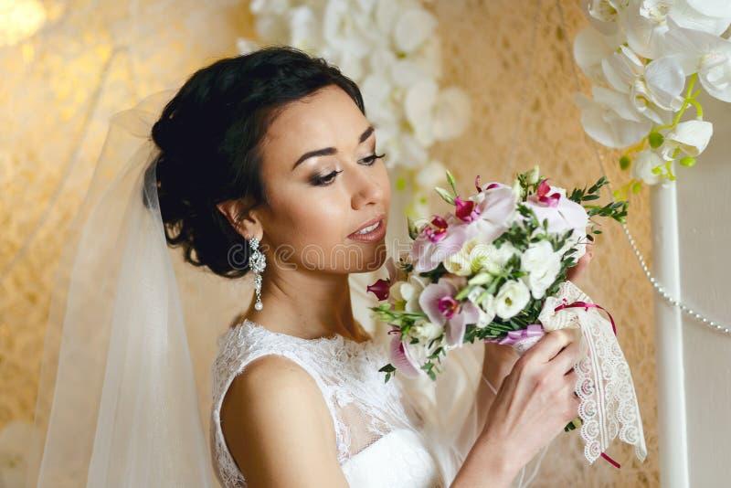 Donkerbruine bruid met huwelijksboeket stock afbeelding