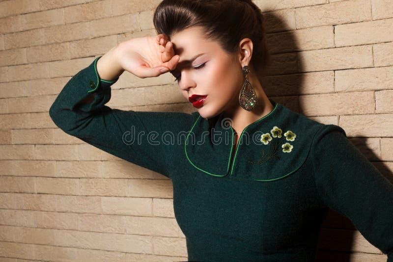 Donkerbruine Droevige Vrouw in Groene Kleding over Bakstenen muur stock afbeelding
