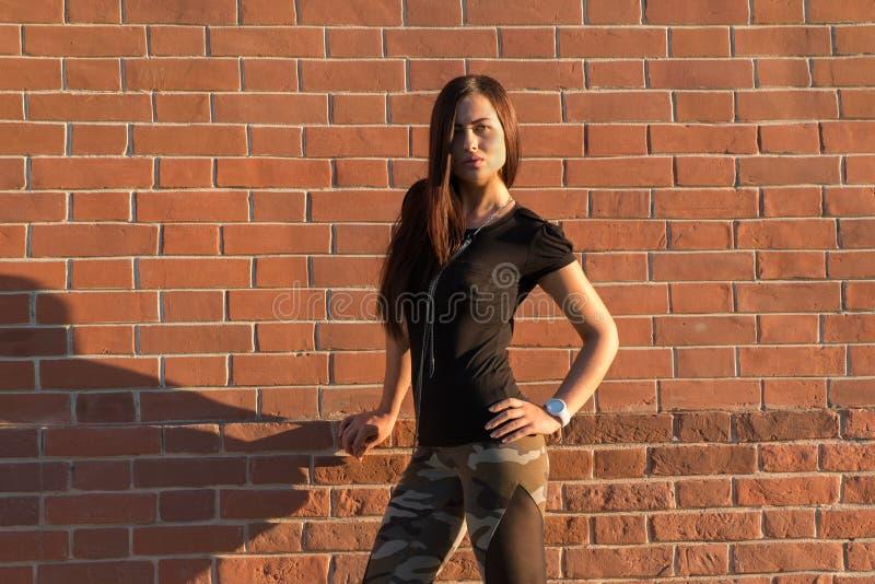 Donkerbruine elegante vrouw voor bakstenen muur backround stock foto's